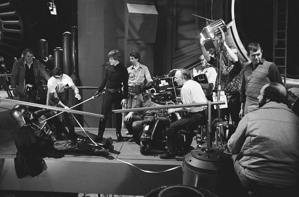 Mark Hamill is filmed during Luke's moment of choice: Will he commit patricide or become a true Jedi and show compassion for his father (Simon Hume stands beside Hamill; assistant camera loader Tony Jackson, in white T-shirt, uses his tape measure; director Richard Marquand is on far right of image; Alec Mills operates the camera; holding the script pages is script supervisor Pamela Mann-Francis; in the foreground is Frank Elliott, bearded; Alan Hume adjusts the light).