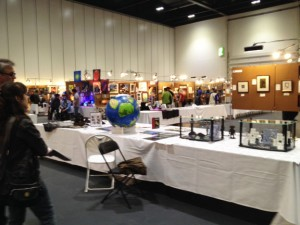 LonCon3 art show with tables intermixed with panels, disolaying art (Angus's imaginary world shown on the table, before 'wrapping)