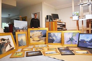 Artist Armand Cabrera, standing behind his paintings, framed and ready for packing for IX7