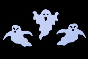 three white ghost outline shapes on black backdrop