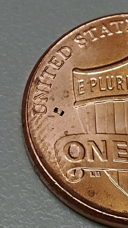 "The microrobot can be seen just to the right of the ""U"" in United States on this U.S. penny. (Purdue University image/Georges Adam)"